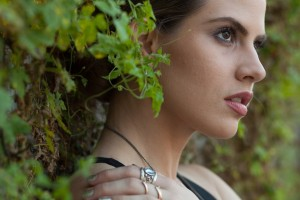 Side profile of girl in leaves wearing MODELLAUNCHER make-up and rings.