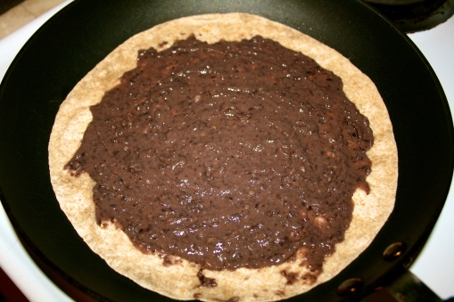 Tortilla with black bean paste in a frying pan.