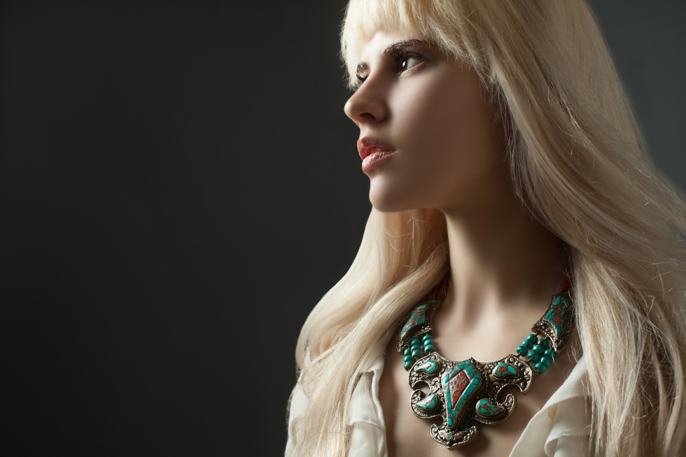 Blonde model wearing funky turquoise jewelry.